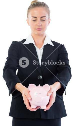 Serious chic businesswoman presenting a piggy bank
