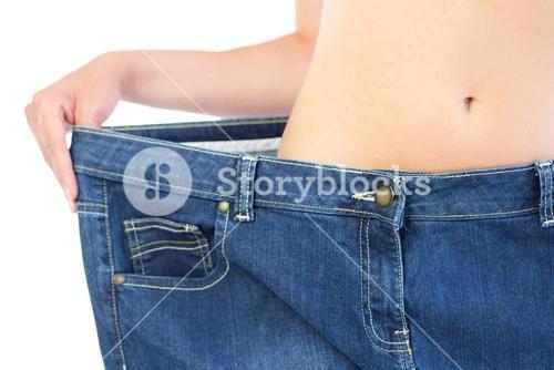 Extreme close up of confident slender blonde wearing too big trousers