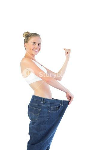 Confident triumphant blonde wearing too big trousers