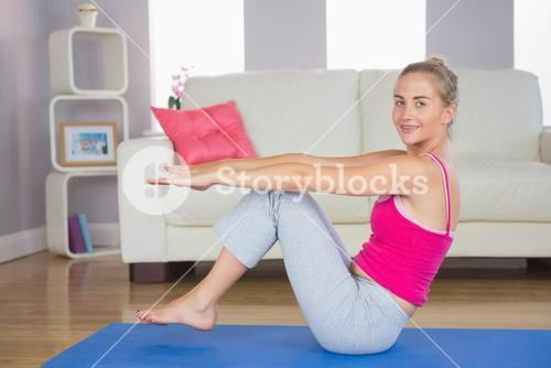 Sporty smiling blonde doing core exercise