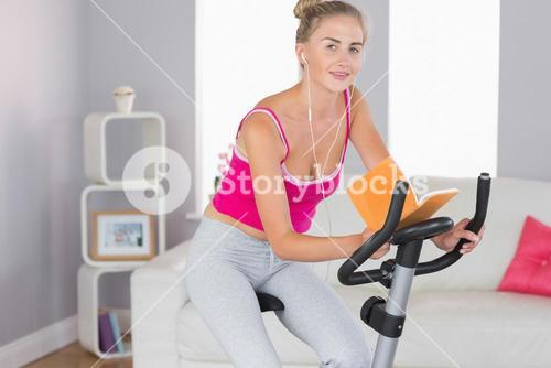 Sporty smiling blonde training on exercise bike reading a book