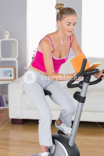 Sporty happy blonde training on exercise bike reading a book
