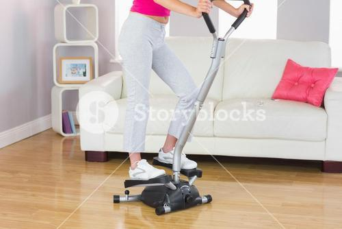 Sporty woman training on step machine