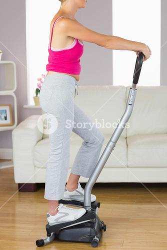 Side view of sporty woman training on step machine