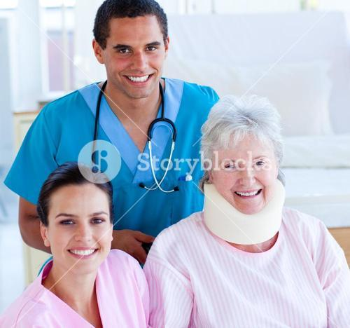 Two smiling doctors taking care of an injured senior woman