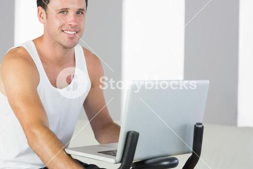 Handsome sporty man exercising on bike and holding laptop