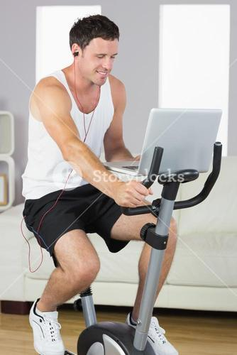 Sporty man with earphones exercising on bike looking at laptop