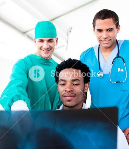Optimistic male doctors looking at XRay