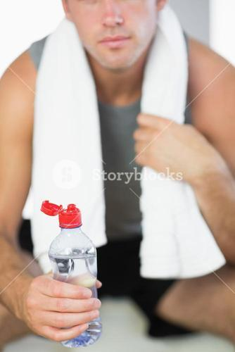 Close up of water bottle held by sporty man