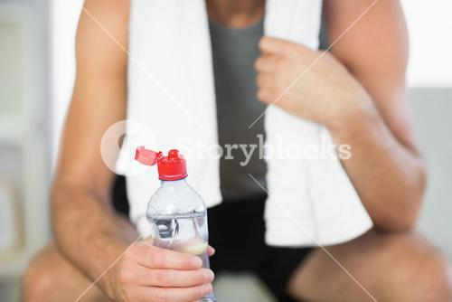 Close up of water bottle held by sporty man with towel