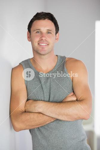 Sporty smiling man leaning against wall with arms crossed