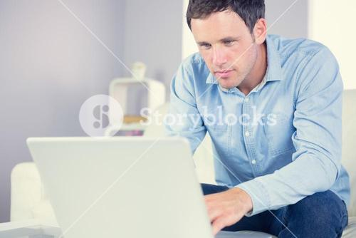 Content casual man looking at laptop