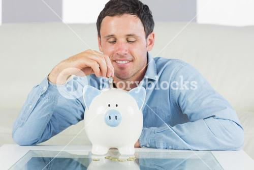 Content casual man putting coin in piggy bank
