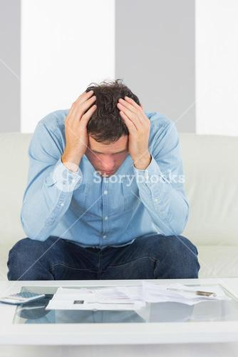 Worried casual man sitting on couch paying bills