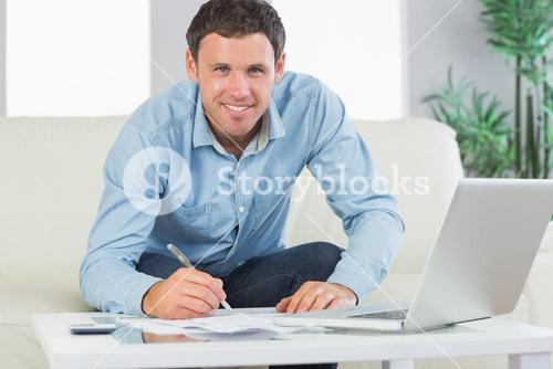 Smiling casual man writing on sheets paying bills