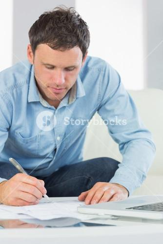 Content casual man writing on sheets paying bills