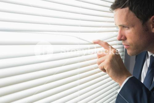 Serious handsome businessman looking through roller blind