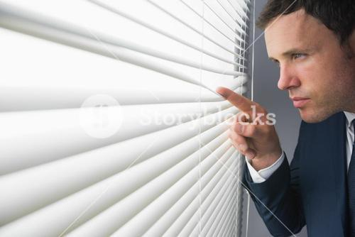 Stern attractive businessman spying through roller blind