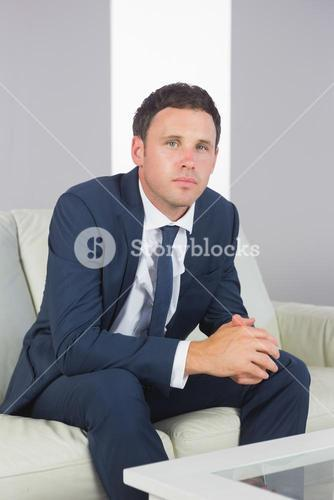 Serious handsome businessman relaxing on couch