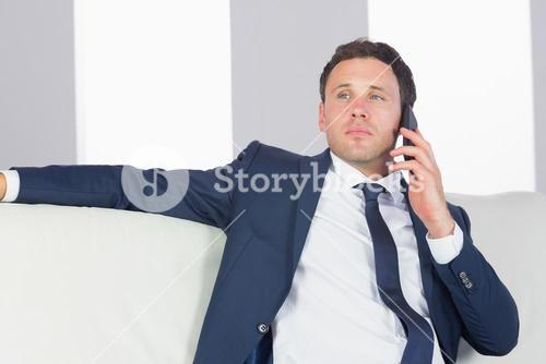 Serious handsome businessman phoning and sitting on couch