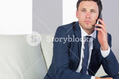 Stern handsome businessman phoning and sitting on couch