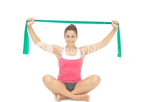 Pretty sporty brunette stretching with resistance band sitting cross legged