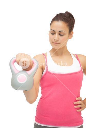 Content sporty brunette holding grey and pink kettlebell