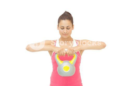 Content sporty brunette holding grey and yellow kettlebell