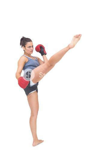Stern sporty brunette kicking in the air