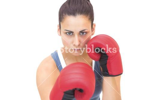 Attractive sporty brunette wearing red boxing gloves