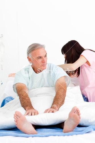 Female nurse adjusting pillows for a senior patient in a hospital