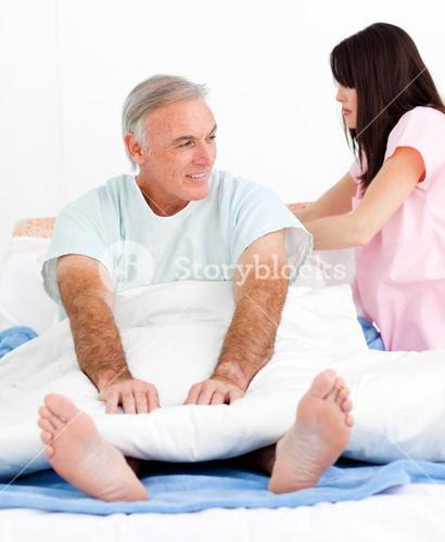 Attentive nurse fixing her patients bed