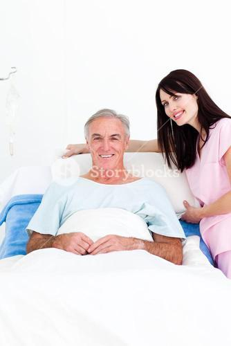 Caring nurse adjusting pillows for a senior patient