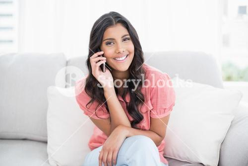 Cheerful cute brunette sitting on couch phoning