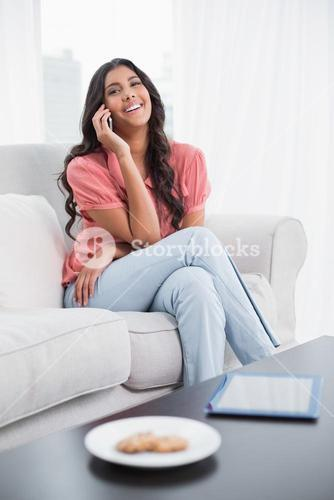 Cheerful cute brunette sitting on couch phoning on smartphone