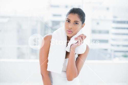 Frowning toned brunette holding towel
