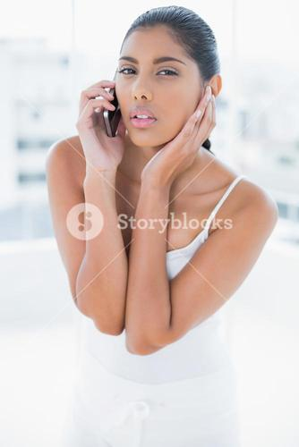 Frowning toned brunette phoning with mobile phone