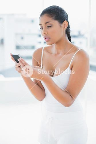 Frowning toned brunette holding mobile phone