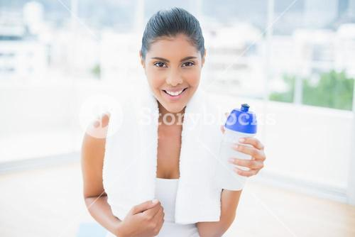 Smiling toned brunette with towel holding sports bottle