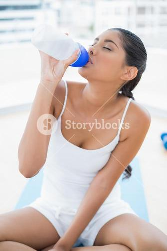 Peaceful toned brunette sitting on floor drinking with closed eyes