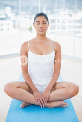 Peaceful toned brunette sitting on floor in lotus pose with closed eyes