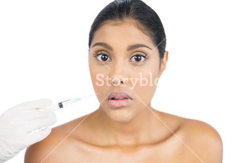 Serious nude brunette holding injection looking at camera