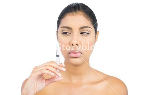 Serious nude brunette holding injection looking at it
