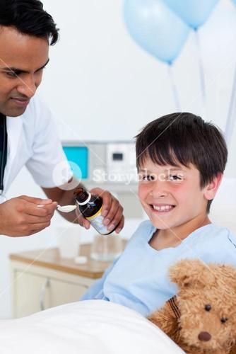 Positive doctor giving medicine to a little boy