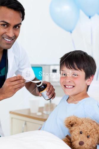 Smiling doctor examining a little boy with his father