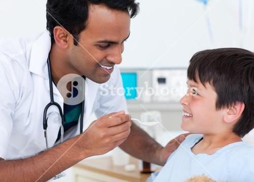 Handsome doctor giving medicine to a little boy