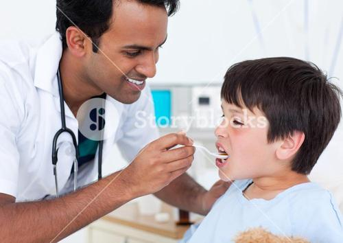 Charismatic doctor giving medicine to a little boy