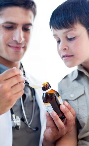 Assertive doctor giving medicine to a little boy