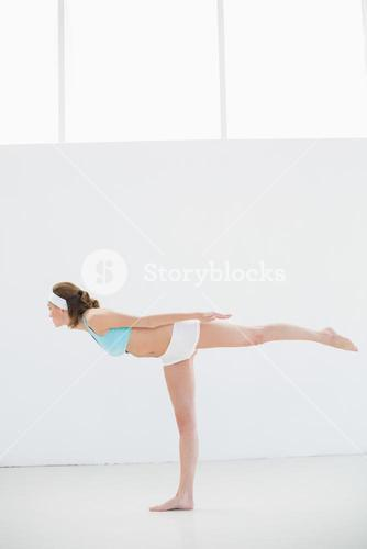 Sporty brunette woman stretching standing in a sports hall
