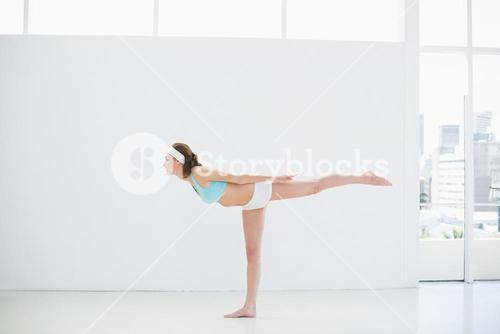 Sporty slender woman doing yoga exercises in a sports hall